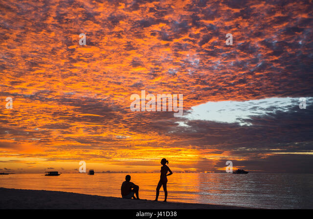 Sunset with two people at Meeru Island Resort, Meerufenfushi, North-Male-Atoll, Maldives - Stock Image