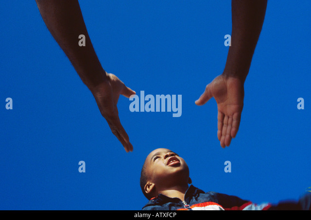 7 year old African American boy leaping into father's hands - Stock-Bilder