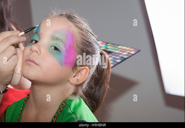 Little cute girl making facepaint before halloween party. The make-up artist is applying some colors while she is - Stock Image