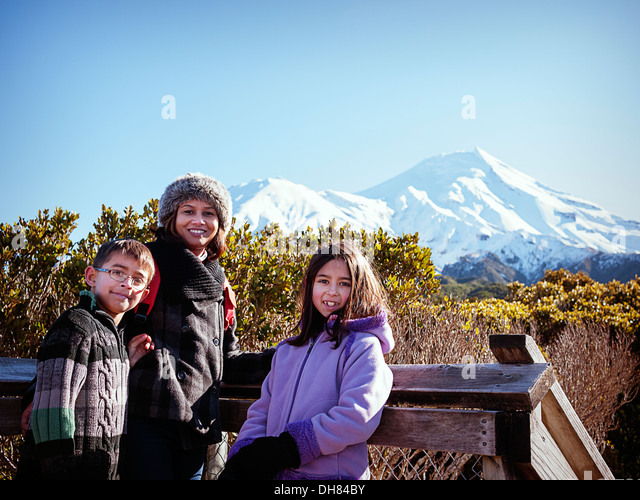 Mother, son, daughter, Taranaki volcano, Mount Egmont, New Zealand, sunny winter day. - Stock Image