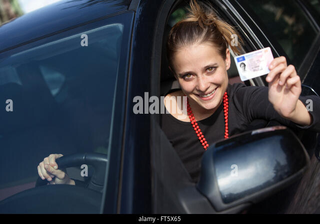Smiling young woman in the car showing her driver's license - Stock Image