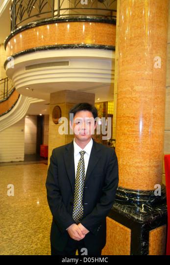 Shanghai China Dianchi Road Huangpu District Manhattan Bund Business Hotel lobby Asian man suit tie manager concierge - Stock Image