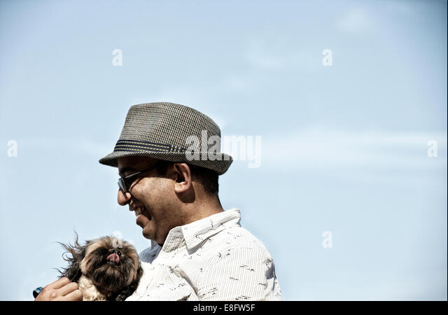 USA, Illinois, Cook County, Chicago, Man playing with dog on beach - Stock Image