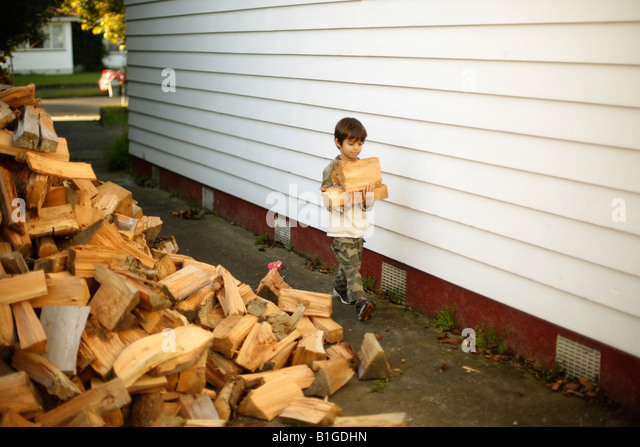 Six year old boy brings logs in from the woodpile - Stock Image
