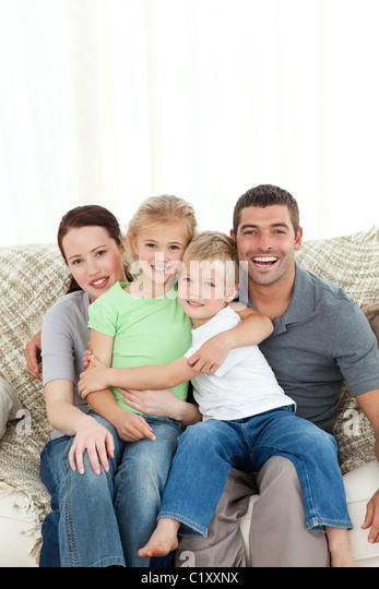 Joyful family sitting on the sofa - Stock Image