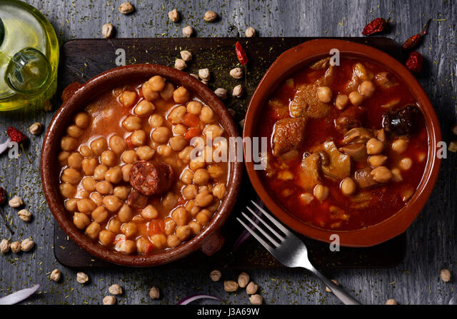 high-angle shot of two earthenware bowls with two typical spanish dishes, potaje de garbanzos, a chickpeas stew - Stock Image