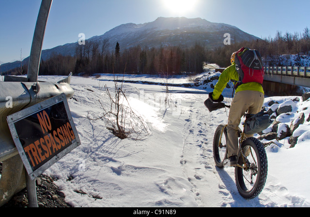 Man biking past a No Trespassing sign along the Knik River to the Knik Glacier on a fat tire bicycle, Chugach Mountains, - Stock-Bilder