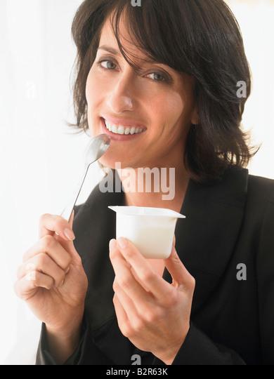 Woman eating yoghurt, smiling - Stock Image