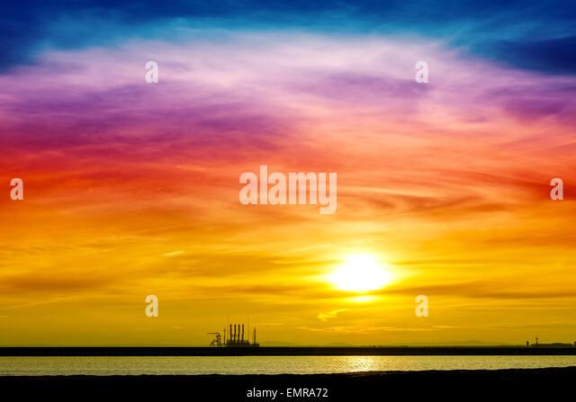 Colorful sunrise over industrial infrastructure in Swinoujscie harbor, Poland. - Stock Image