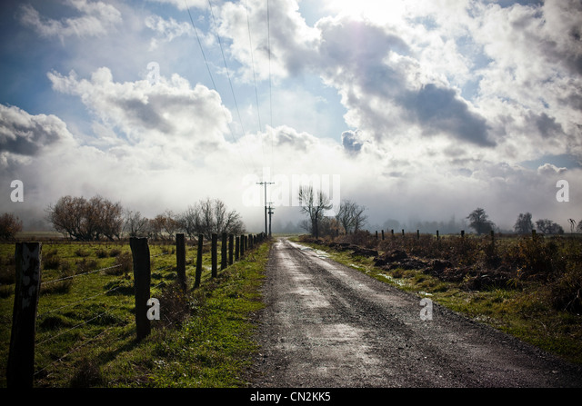 Rural road with fence and clouds in sky - Stock Image