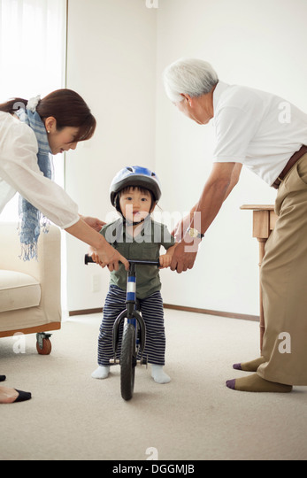 Boy learning to ride bicycle - Stock Image