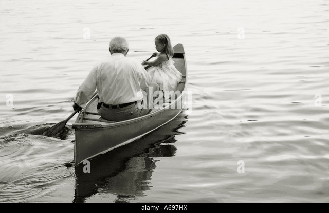 Grandfather and granddaughter paddling in canoe on lake. - Stock Image