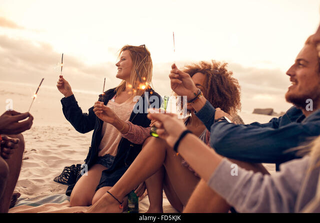 Group of friends having fun with sparklers outdoors at the beach. Diverse group of young people celebrating new - Stock Image