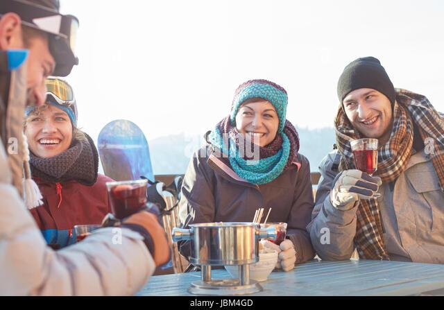 Snowboarder friends drinking cocktails on sunny patio apres-ski - Stock-Bilder