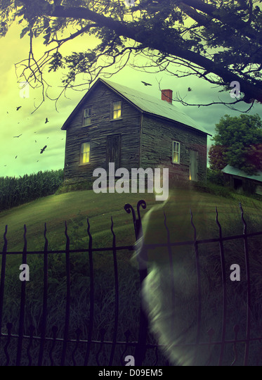 Abandoned haunted house on a hillside with ghost - Stock Image
