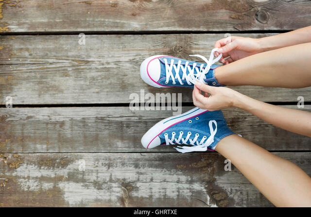 Young woman tying laces of her jeans sneakers sitting on the wooden floor - Stock-Bilder