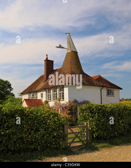 Unusual looking old Oast house with a square and round roof. - Stock Image