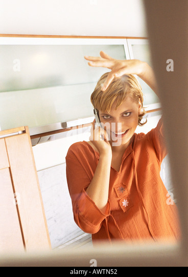 Teen girl using cell phone and fixing hair in mirror - Stock Image