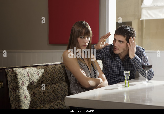 Couple arguing in a bar. - Stock Image
