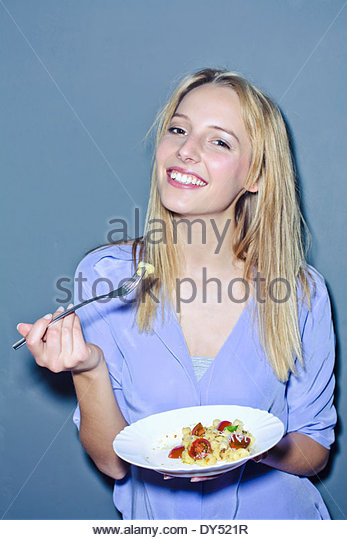 Young woman holding plate of food - Stock-Bilder