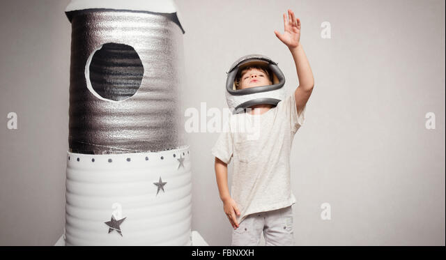 Happy child dressed in an astronaut costume playing with hand ma - Stock Image