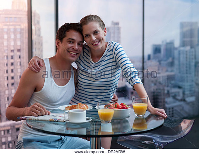 Couple hugging with breakfast on the table - Stock-Bilder