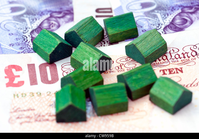 Toy houses sitting on pound notes representing house prices or financial services connected with the housing market. - Stock Image