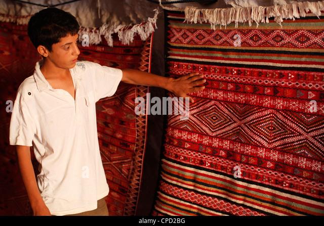 Boy showing a rug in a carpet shop, Toujane, Tunisia, North Africa, Africa - Stock-Bilder