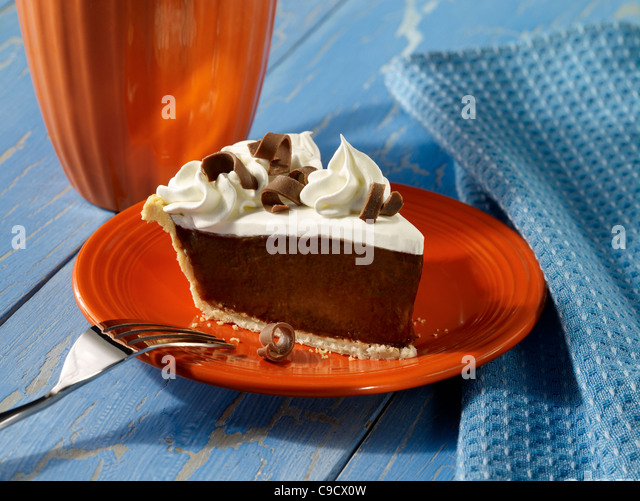 A slice of chocolate cream pie topped with whip cream and chocolate curls - Stock Image
