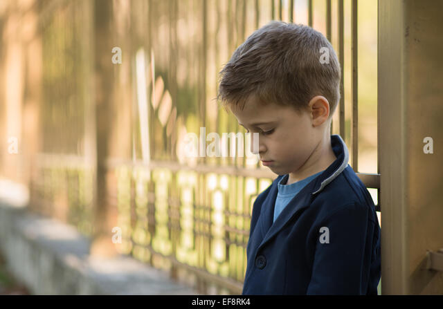 Portrait of a sad boy leaning against metal railings - Stock Image