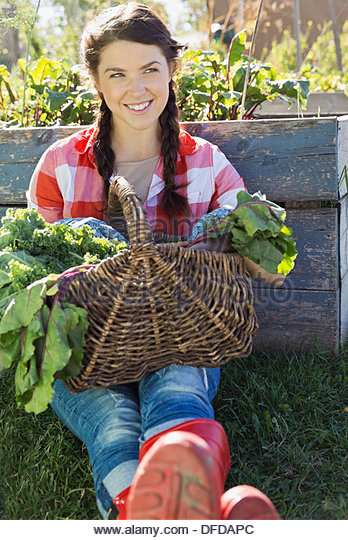 Woman sitting with vegetable basket in community garden - Stock Image