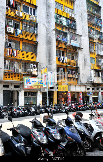 scooters parked in street before buildings, Macau, China - Stock Image