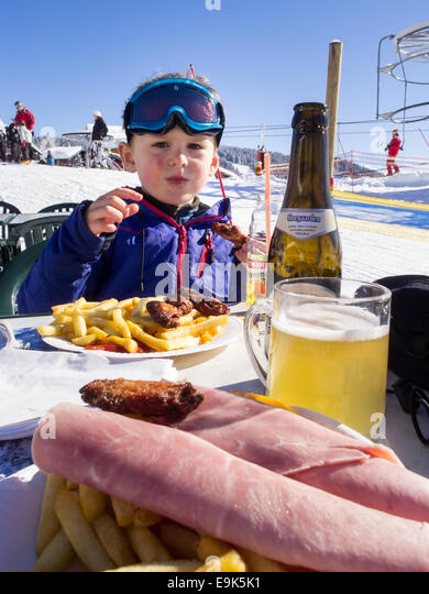 small boy in ski clothes eating at an outdoor table next to a ski piste with beer and food in foreground - Stock Image