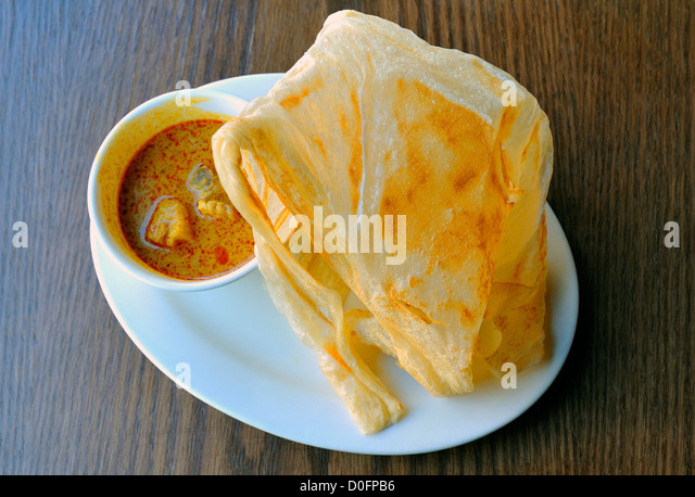 Roti canai, a Malaysian - Indonesian appetizer of a thin Indian pancake and spicy dip Stock Photo