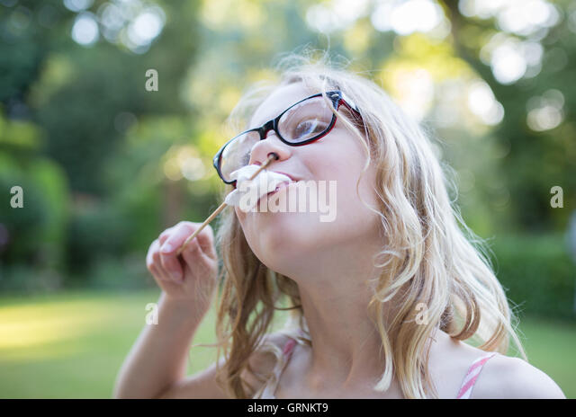 Girl eating marshmallow off a stick - Stock Image