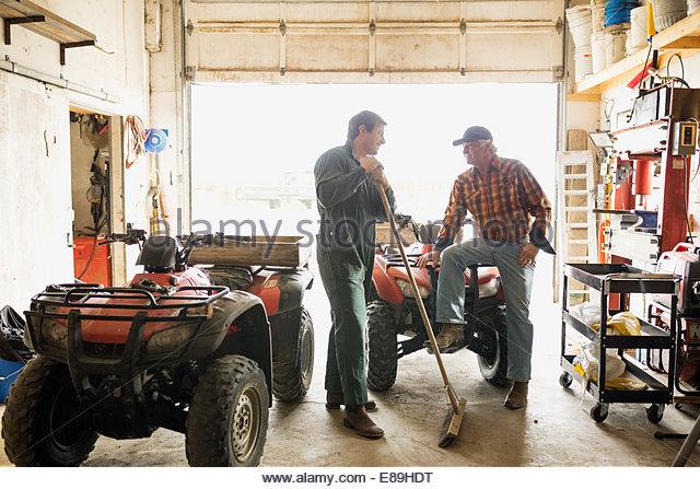 Men talking near quadbikes in garage - Stock Image