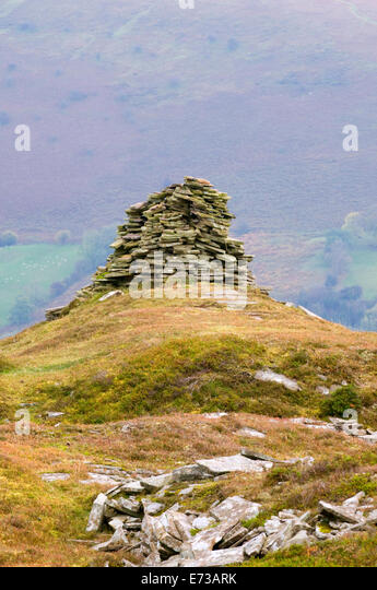 Cairn, flat grey slate stone rock pile, placed artistically on a Lake District hillock outcrop in memory of some - Stock-Bilder