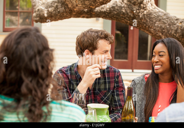 Friends with drinks at backyard barbecue - Stock Image
