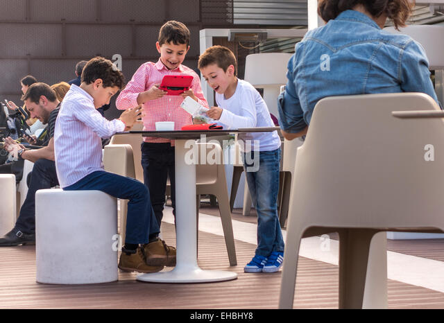Children playing handheld computer games while grown ups, parents, are all looking at their smartphones on a Sunday - Stock Image