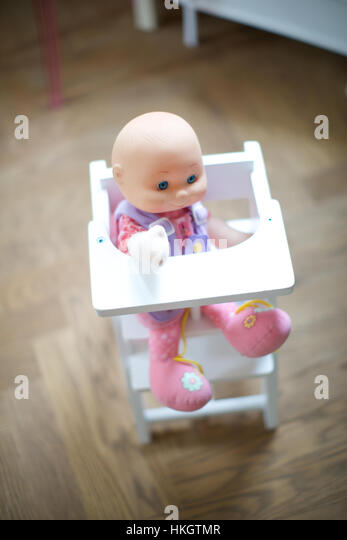 doll in baby chair. toy, children's room, wooden floor, childhood. - Stock Image