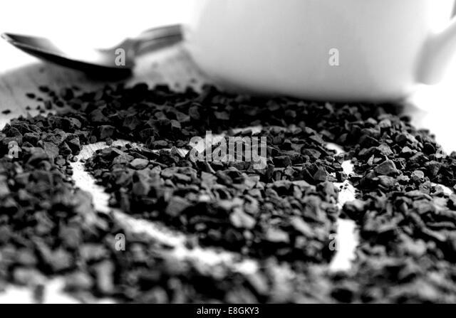 A heart drawn in coffee granules alongside a small silver spoon and white mug - Stock-Bilder