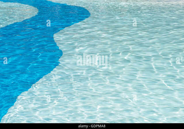crystal clear cool swimming pool background with sun reflection ripples in a two tone blue solid curve patten,ideal - Stock Image