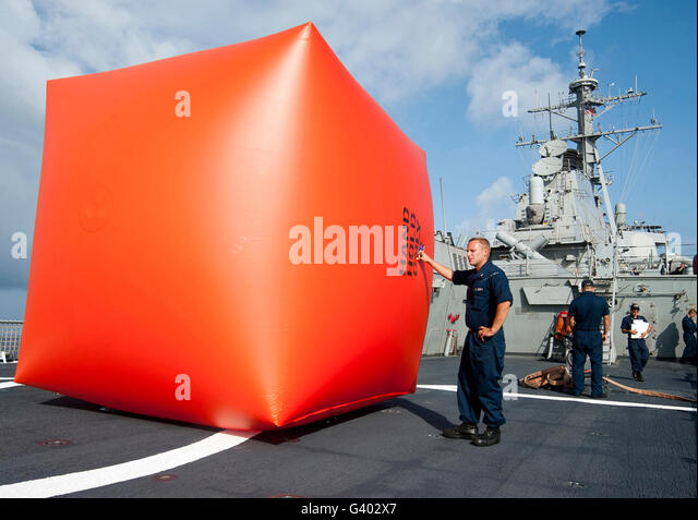 Sailors prepare to deploy a killer tomato for a gunnery exercise aboard USS Decatur. - Stock Image