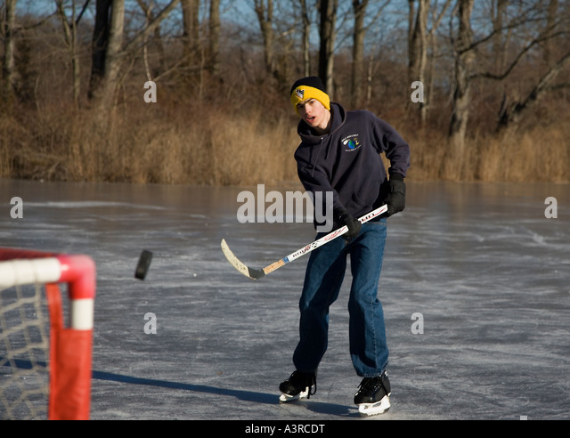 Playing ice hockey on a frozen pond - Stock Image