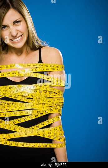 Woman wrapped in measuring tape - Stock Image