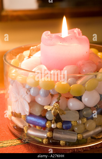 Lit candle in a bowl of beaded jewellery - Stock Image