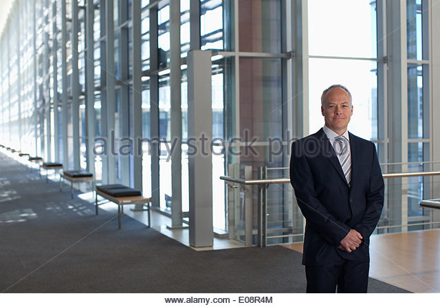 Businessman at window in office lobby - Stock Image