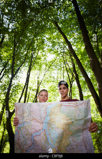 young man and woman checking map during hiking excursion and look for destination. Vertical shape, low angle view - Stock Image