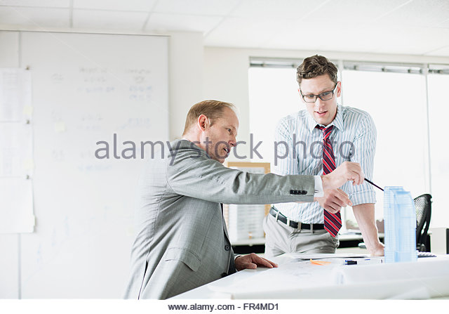 architects in discussion around model buildings - Stock Image