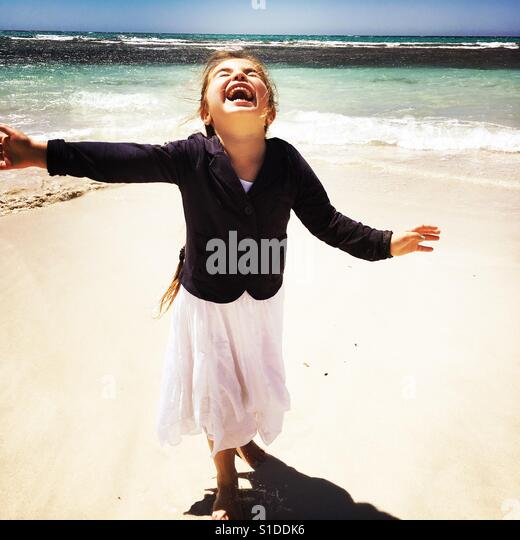 Smiling child running on a white sandy beach - Stock Image
